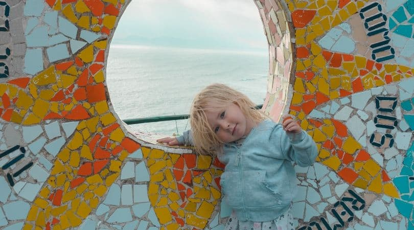 toddler next to sunshine mosaic in parque del amour in lima peru